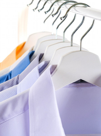 Close Up of Men's dress shirts, Clothes on hangers on white background